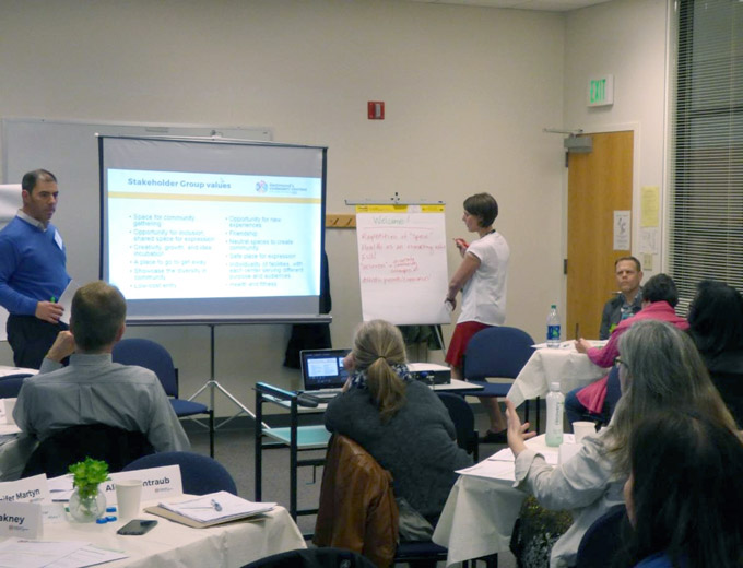 Members of the Redmond Community Centers Stakeholder Group in 2017 are sitting in a meeting in a room with tables and a presentation on a projector screen. Six people are listening to a man present at the front of the room. A woman is writing on a flipchart at the front of the room next to the presentation.