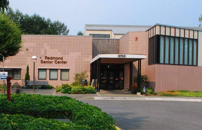 The main entrance of the old Redmond Senior Center is shown during the daytime from the outside. There is landscaping in the form of bushes and trees, as well as a bench and pole with a light on top.