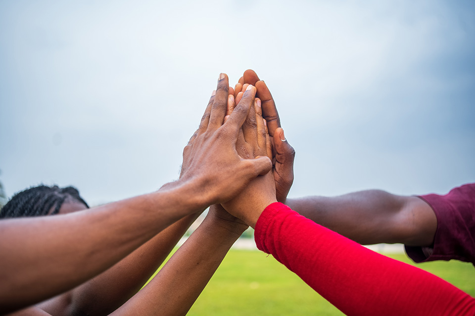 A group of people join hands in solidarity to show support for each other and a single goal.