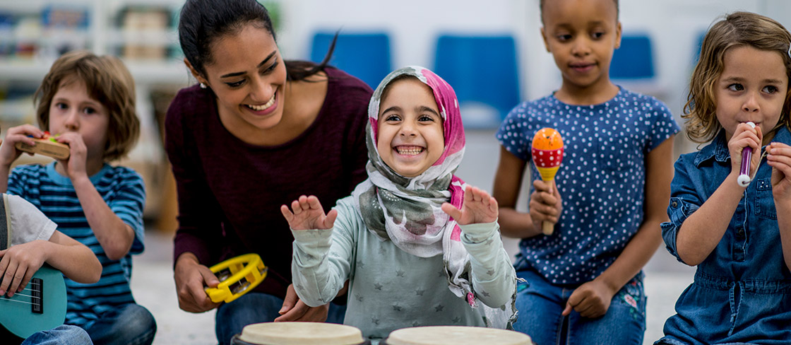 An adult and five kids with diverse ethnic backgrounds play various instruments, including a ukulele, drums, shaker, tambourine and kazoo. The adult and one of the kids are smiling.