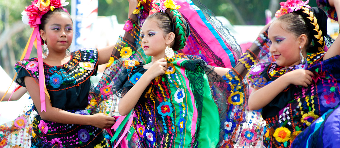 Three youths of Hispanic or Latin-x background are in colorful makeup and dresses featuring shapes and flowers. They are dancing outside.